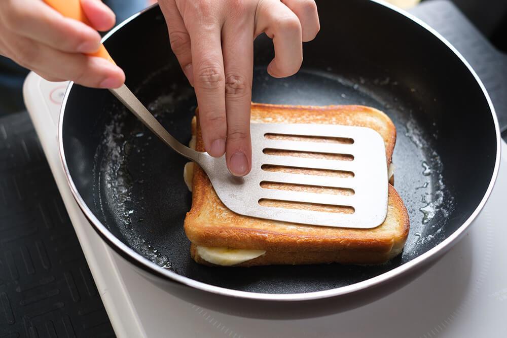 パンをフライ返しで押さえているところ