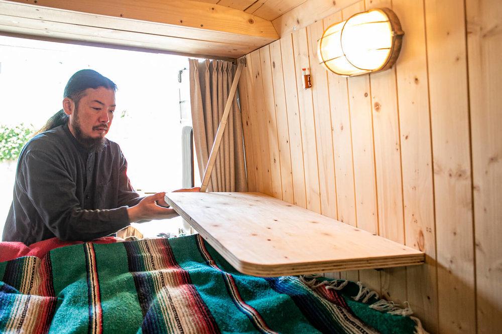 折りたたみ式の棚を下ろす鈴木さん