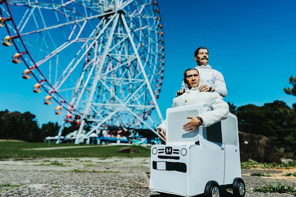 公園で大きな観覧車をバックに、ミフネカーに乗ったミフネさんとヨシダさんが遠くを見ている