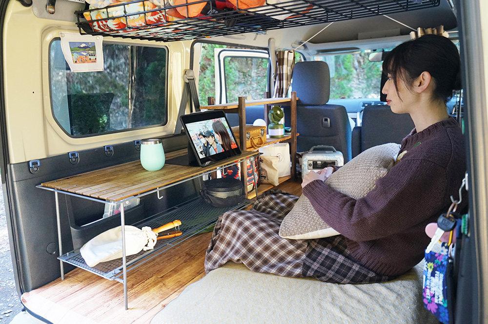 車内のテーブルで動画を見る森風美さん