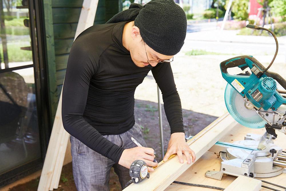 車中泊DIYカスタムでテーブルとベッドを作る。観音クリエイションが木材をメジャーで測っている