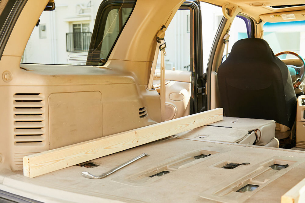 車中泊DIYカスタムでテーブルとベッドを作る。車室に木材を置いて確認している