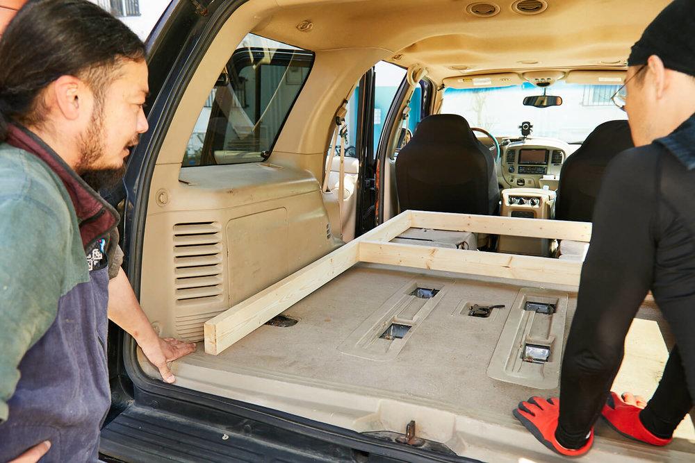 車中泊DIYカスタムでテーブルとベッドを作る。車室に木枠を置いて確認している