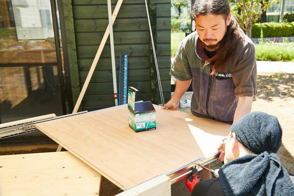 車中泊DIYカスタムでテーブルとベッドを作る。スライドレールの内側に天板をはめているところ