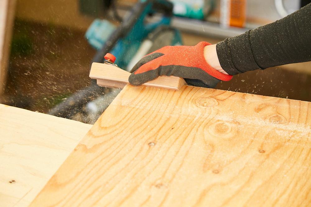 車中泊DIYカスタムでテーブルとベッドを作る。ベッドの床板の角を面取りしているところ