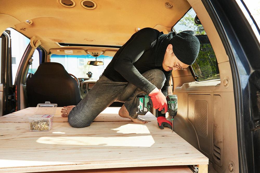 車中泊DIYカスタムでテーブルとベッドを作る。ベッドの床板を木枠に打ち付けているところ