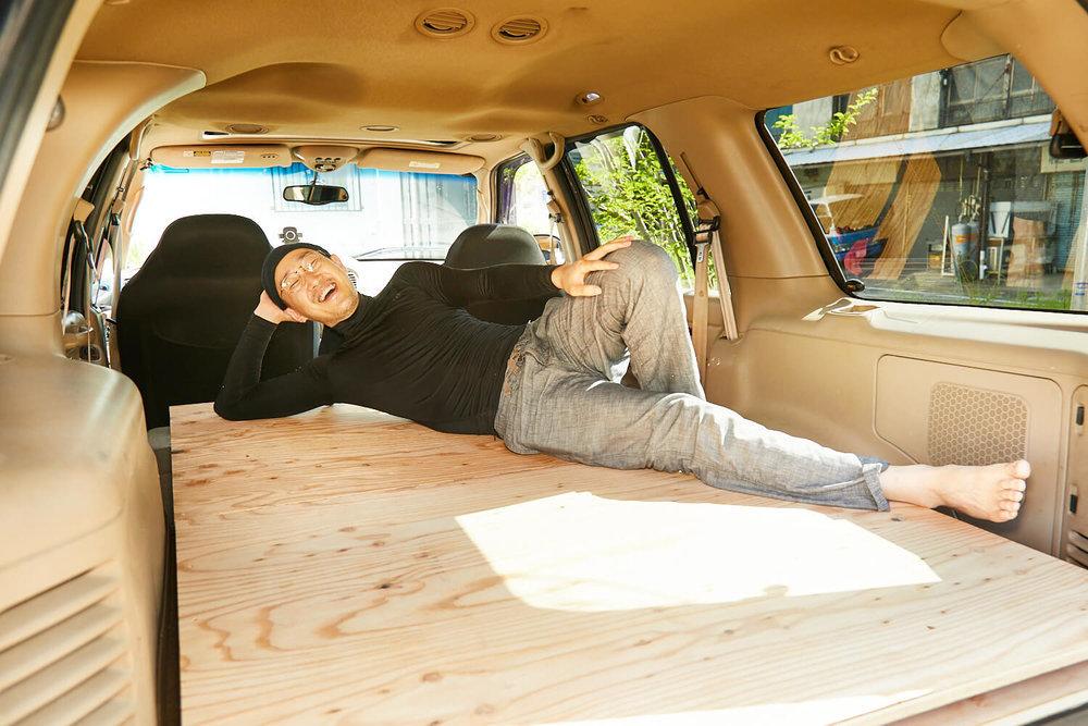 車内にセットしたベッドの上に寝転ぶ観音クリエイション