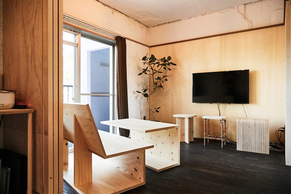 鈴木さん手作りのテーブル、ソファ、スツールが並んだ室内