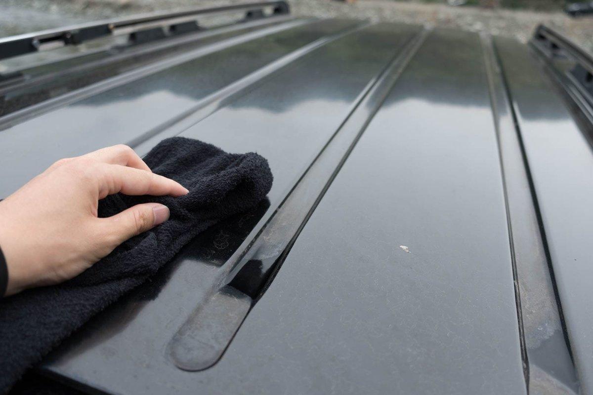 クルマの屋根をタオルで拭いている