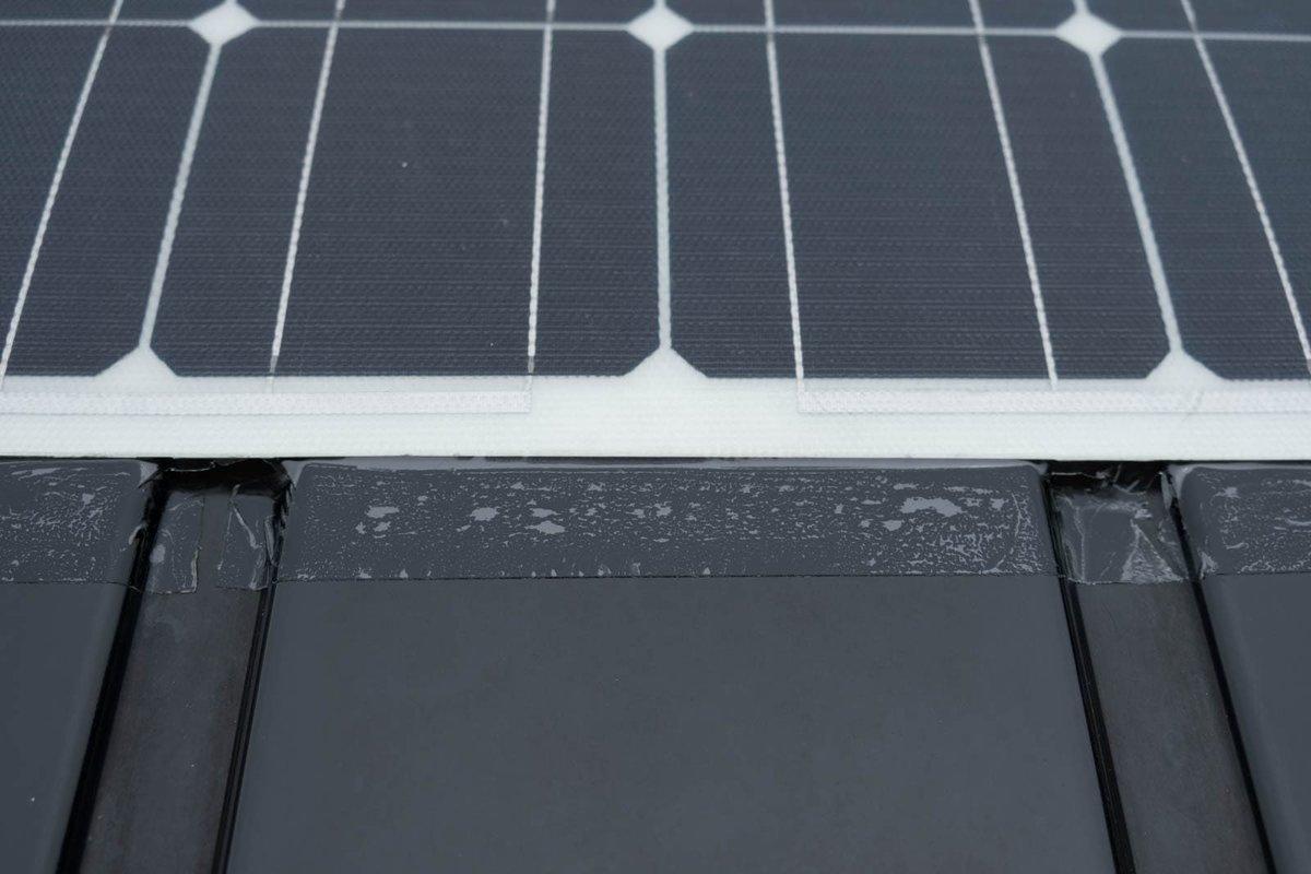 ソーラーパネルの四辺を強力補修テープで屋根に貼り付ける