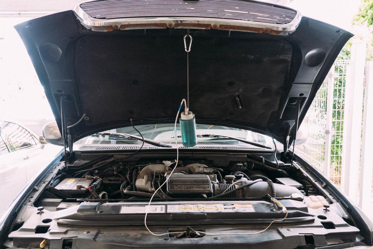 容器をボンネットに吊るして洗浄液をエンジンに注入しているところ