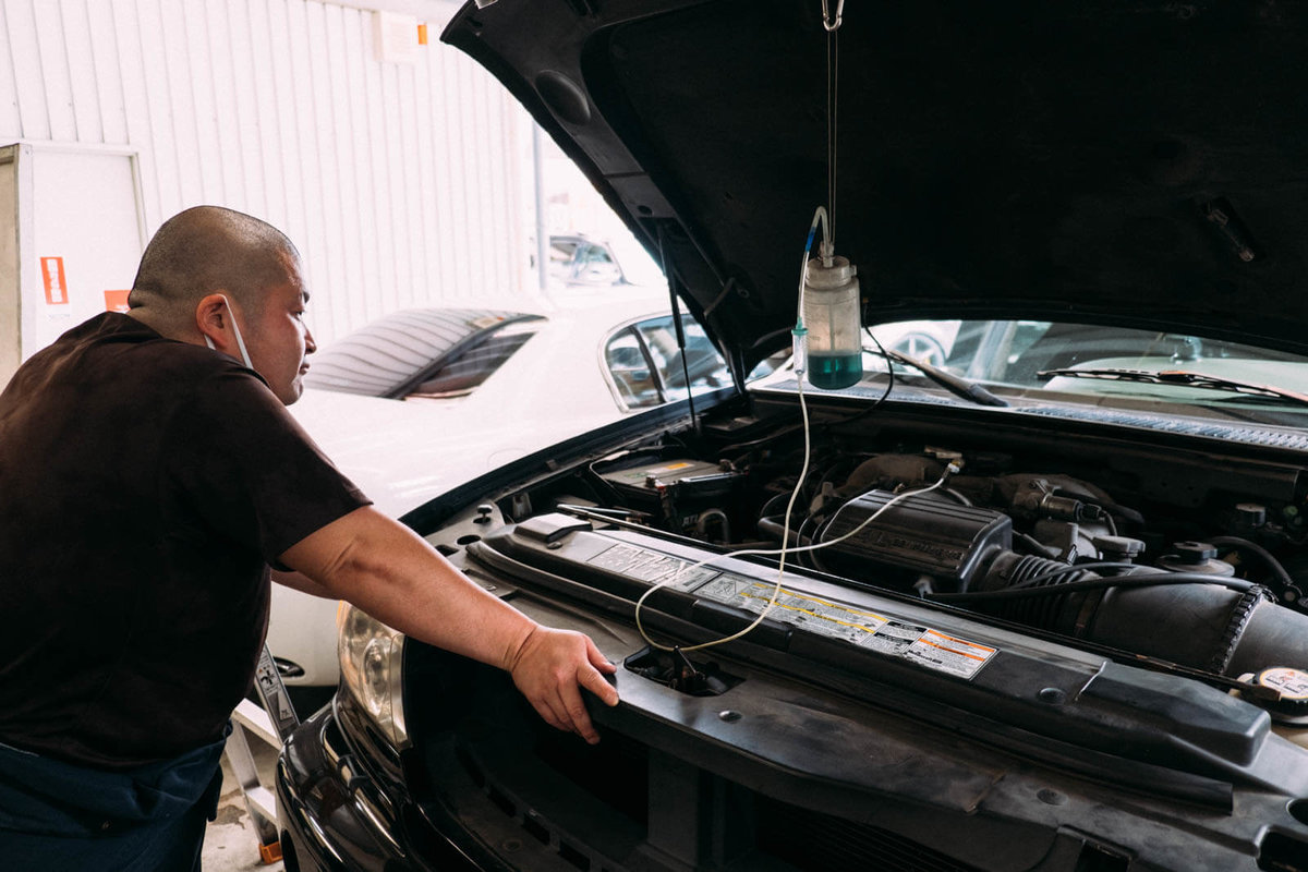 洗浄液をエンジンに注入するところを見ているカースピリッツの今本店長