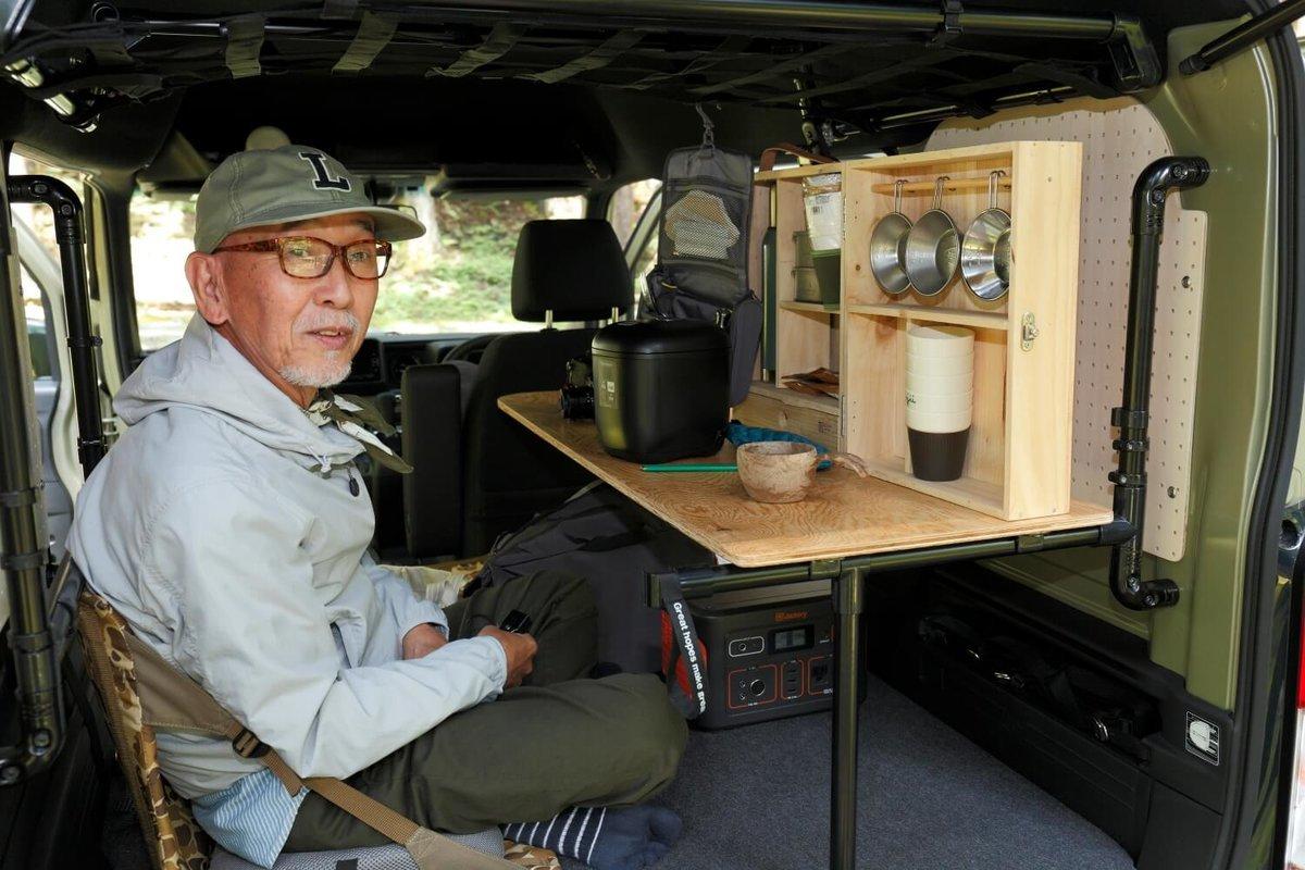 N-VANの荷室に自作のテーブルを設置して座っているウィンピージジイさん。N-VAN車中泊キャンプ、改造カスタム