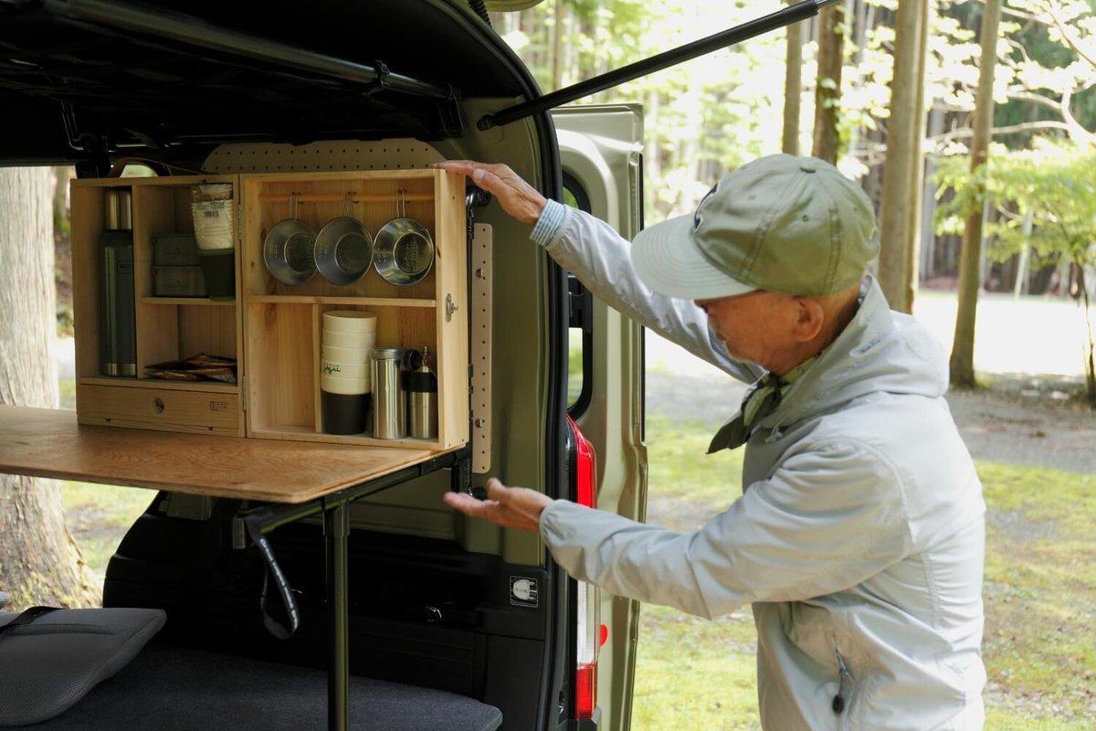 キャンプボックスに触れているウィンピージジイさん。N-VAN車中泊キャンプ、改造カスタム
