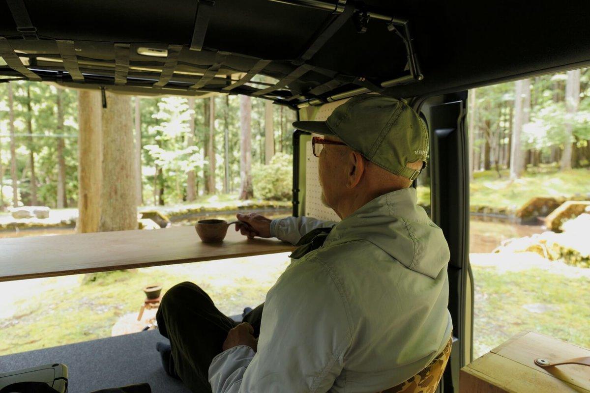 リアゲートを開けて車内から外を見ている。N-VAN車中泊キャンプ、改造カスタム