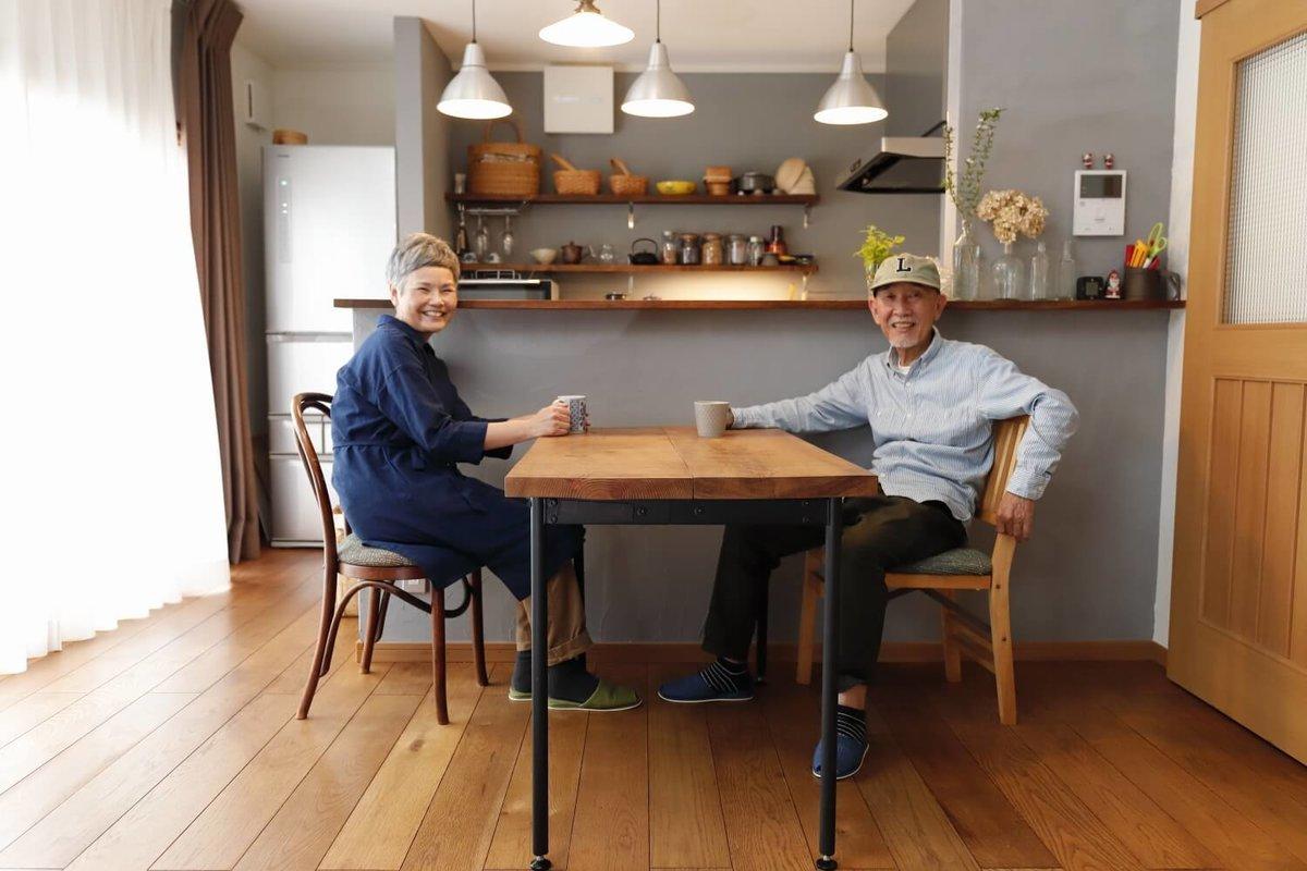 ダイニングテーブルに向かい合って座る笑顔のウィンピージジイさんと奥様