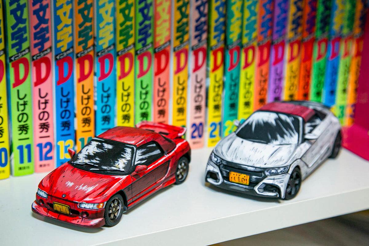 しげの秀一先生の人気マンガ『頭文字(イニシャル)D』とマンガ風塗装カープラモデルが本棚に並んでいる