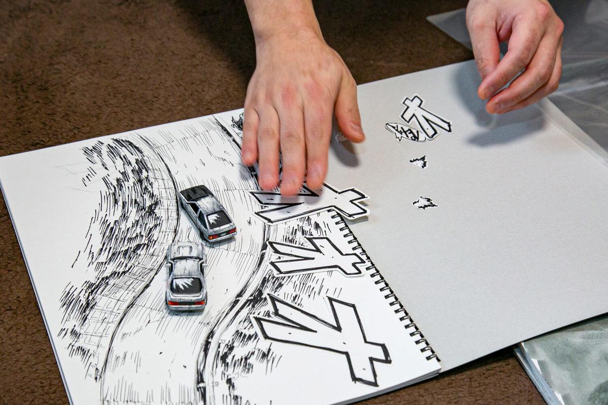 マンガ風塗装ミニカーが本当に走っているかに見えるように道路の絵を描き効果音をそえている
