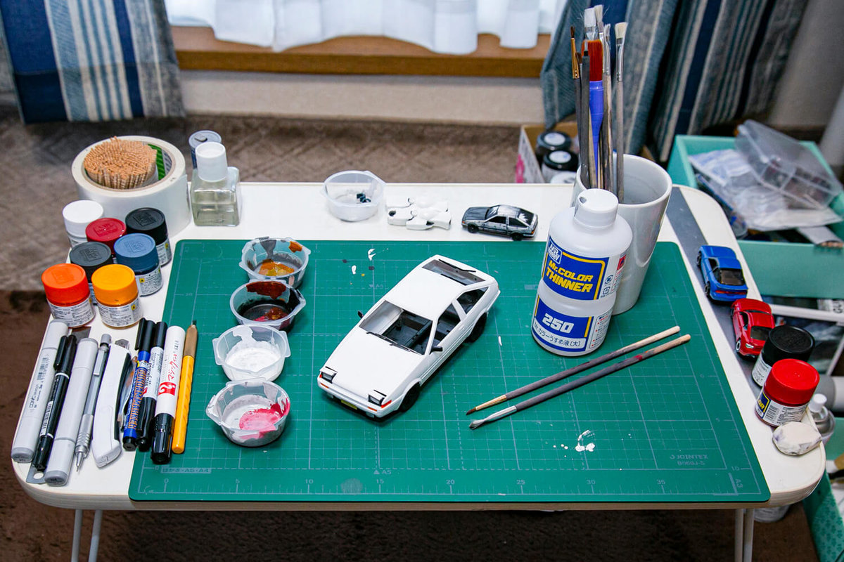 マンガ風塗装カーモデルを制作している作業場、机の上に塗料や筆