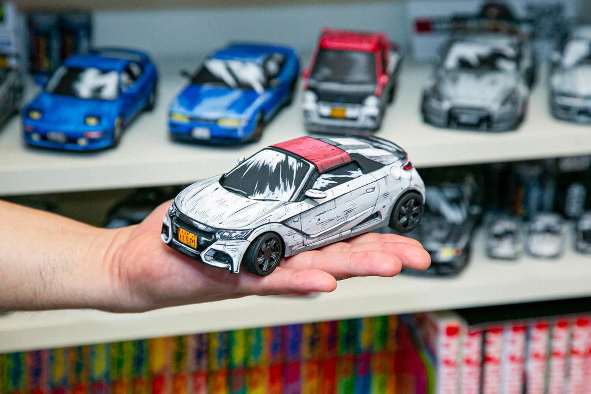 (alt)SHINGAさんが自作のマンガ風塗装カーモデル、ホンダの純正コンプリートカー「S660 Modulo X」を手に持っている