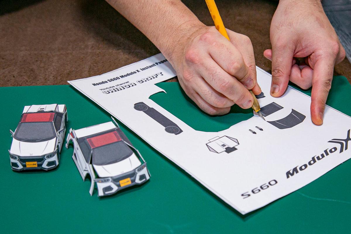 SHINGAさん作のペーパークラフト S660 Modulo Xの作り方を説明。カッティングボードの上で、タイヤとカスタムパーツをカッターで切っている