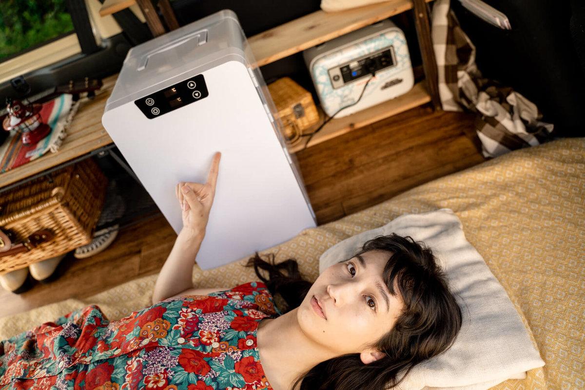 12_車中泊用にカスタムしたバモスの中で寝ている森風美さん。すぐ横にポータブル冷蔵庫(車載冷蔵庫)がある