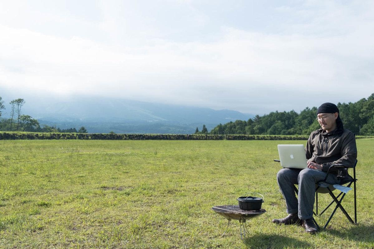 10_車中泊キャンプでバーベキュー。お肉を煮込みながら、焚き火の前で仕事をしている観音さん