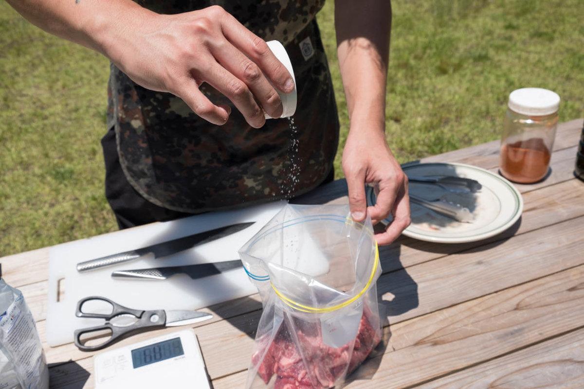 18_車中泊キャンプでバーベキュー。ジップロックの中の牛肉に塩を振っている