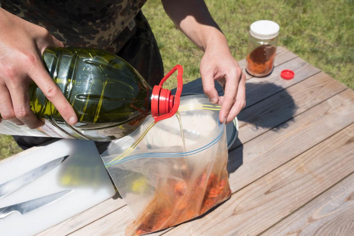 22_車中泊キャンプでバーベキュー。ジップロックの中にオリーブオイルを注いでいる