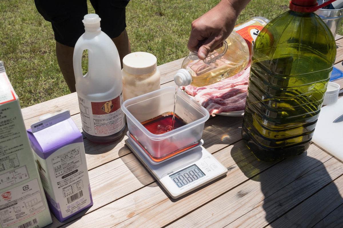 15_車中泊キャンプの調理道具とおすすめ調味料。キッチンスケールで計りながらジップロックコンテナーにみりんを注ぐところ