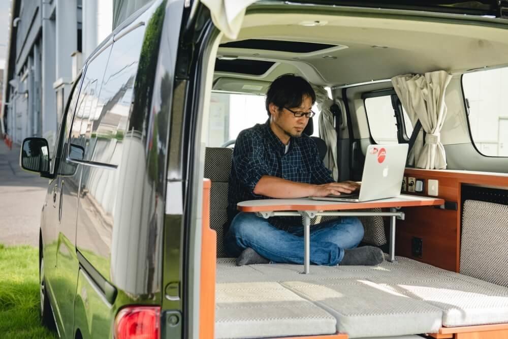 日産「NV200バネット」をベースに製作されたキャンピングカー「キャネル」で仕事をするカーネル編集長の大橋 保之さん