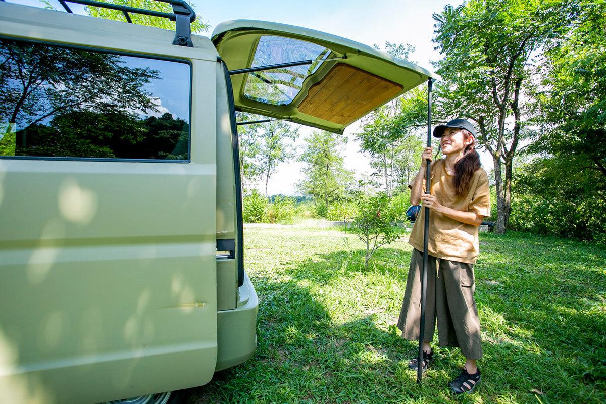 25 レトロなカスタムカー。キャンプコーディネーターの三沢真実さん。スズキ・エブリイのバックドアを開けてポールで固定しているところ