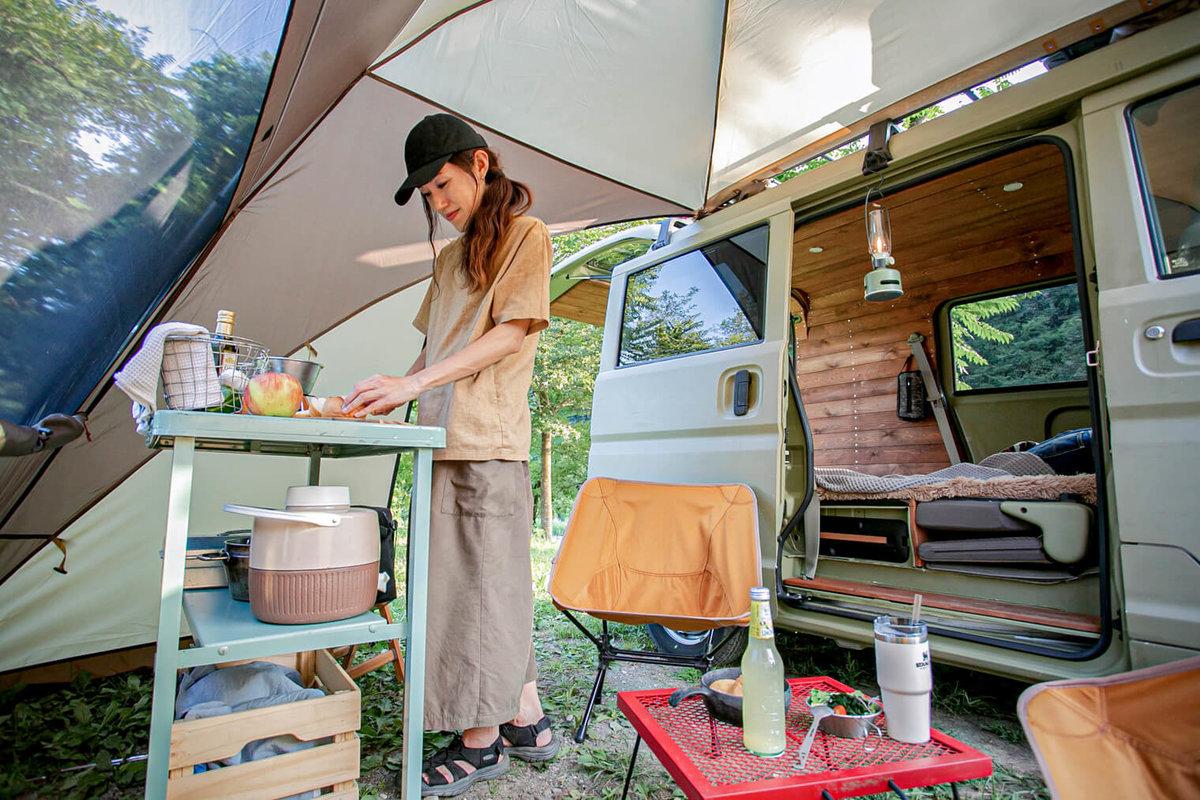 40  レトロなカスタムカー。キャンプコーディネーターの三沢真実さん。カーサイドシェルターの中で料理をしている。おしゃれなインテリア