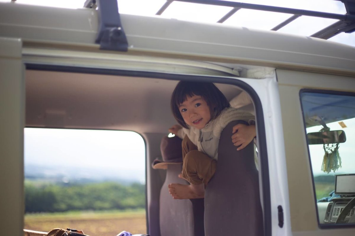 42  レトロなカスタムカー。キャンプコーディネーターの三沢真実さん。2018年夏、車中泊の旅の途中、北海道にて。息子のアリくんがシートのあいだから顔を出している