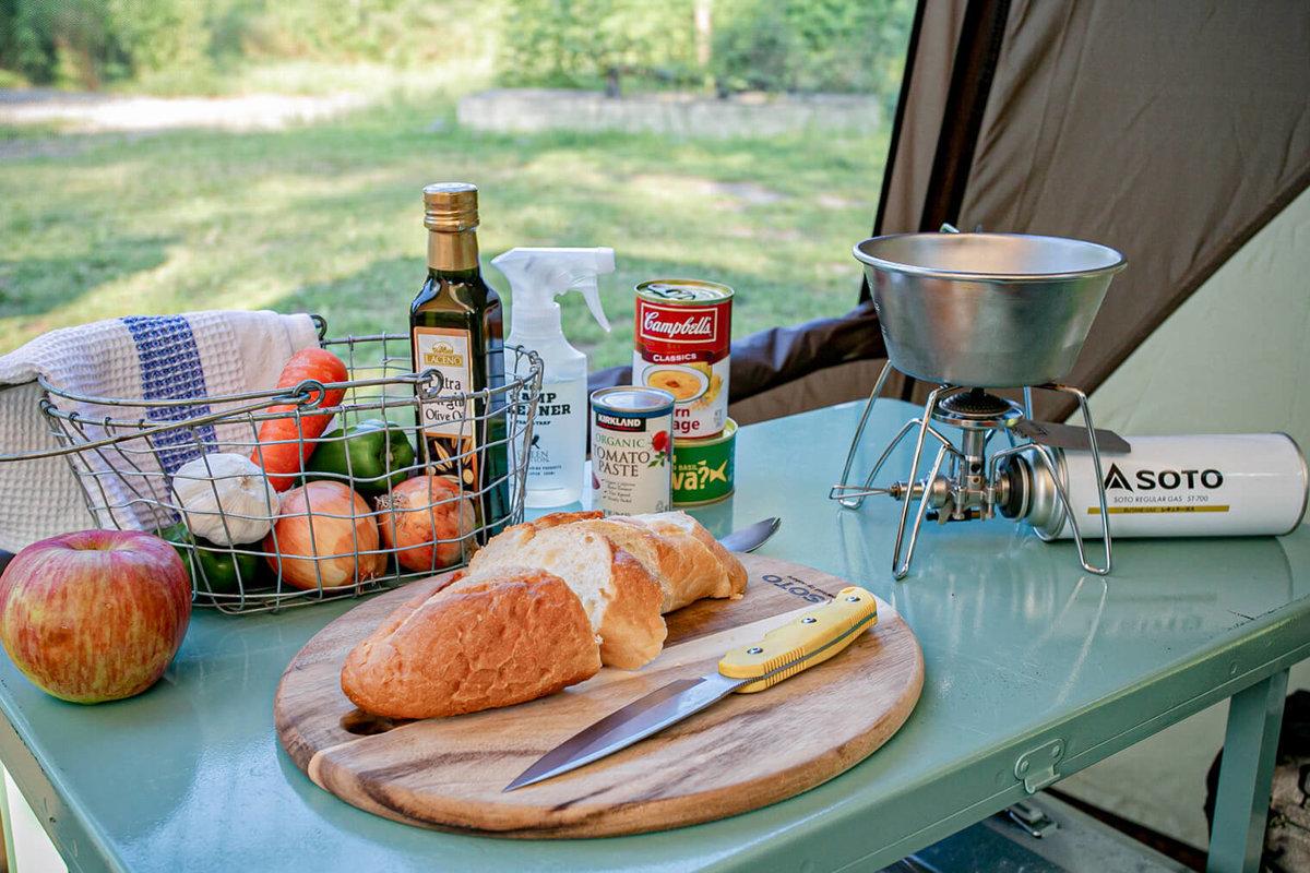 44 レトロなカスタムカー。キャンプコーディネーターの三沢真実さん。カーサイドシェルターの中、食材やセンスのいい調理道具が並ぶ