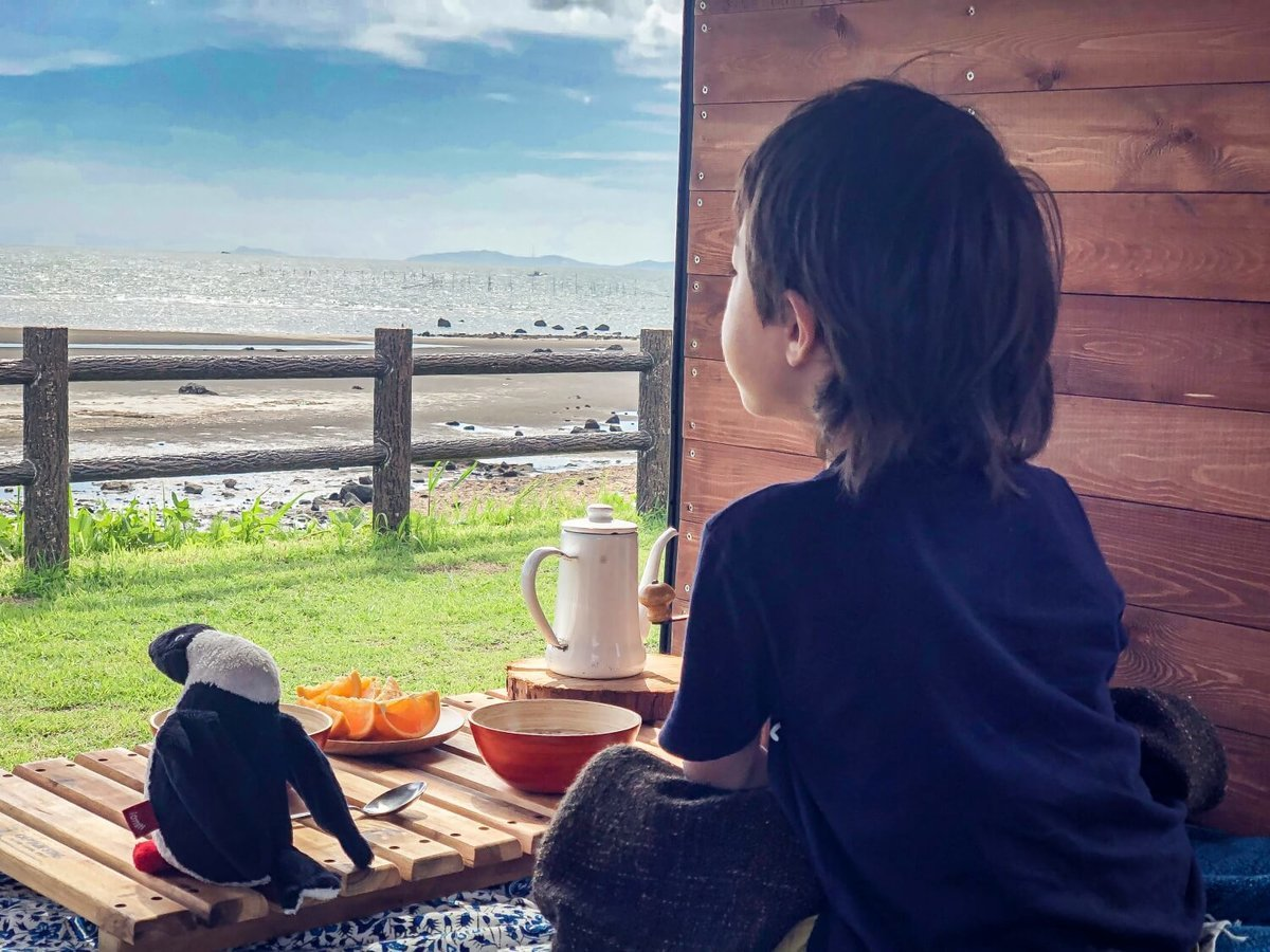 50 レトロなカスタムカー。キャンプコーディネーターの三沢真実さん。2019年、3回目の車中泊の長旅、大分県にて。車内から外を見ている息子のアリくん