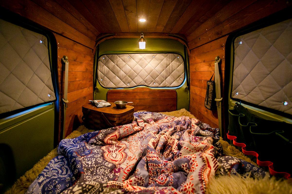 51 板張りのバンライフ仕様におしゃれにカスタムしたスズキのエブリイの車内。キャンプコーディネーターの三沢真実さんのクルマ。窓に目隠しシェードをつけ、ランタンの灯りがともった車内