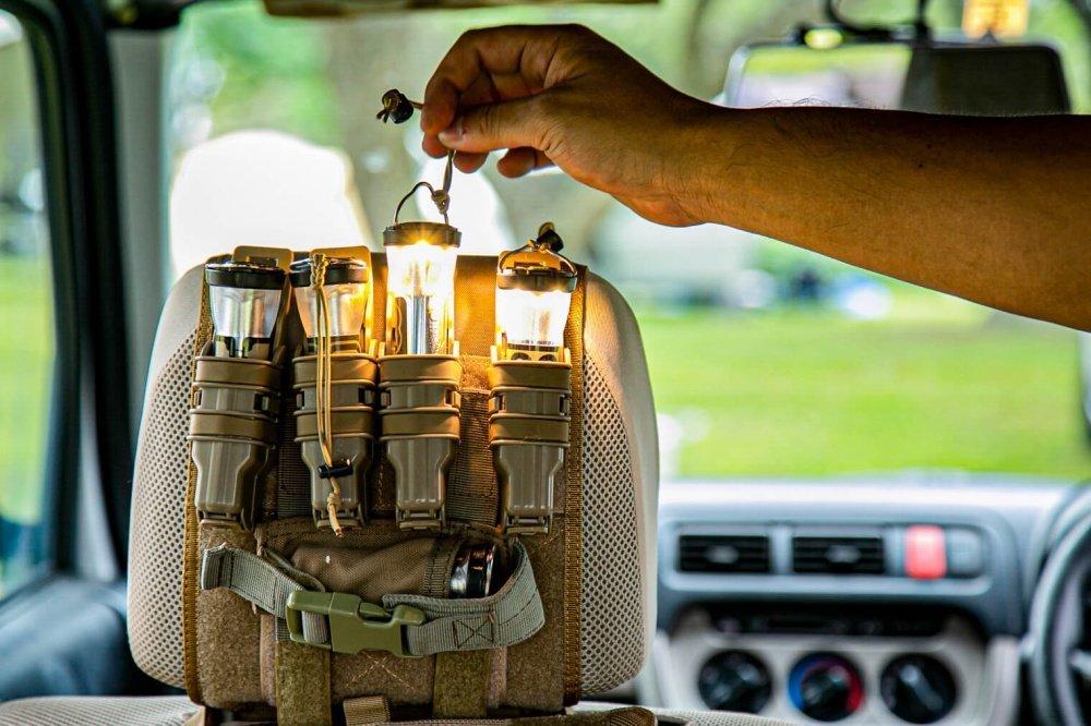 34_Honda・アクティバンの前列シートヘッドレスト(助手席側)に寄った写真。取り付けられた道具入れのマガジンケースに入ったランタンを取り出している