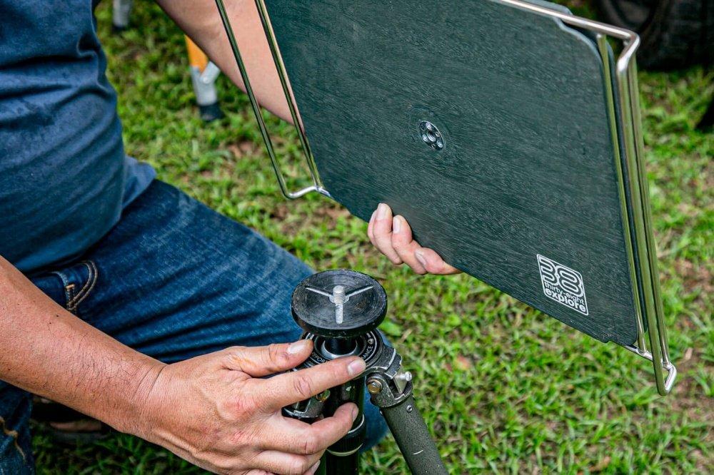 46_宮崎秀仁さんのアウトドアブランド「38explore」のテーブル「38パレット」。テーブル裏面のネジ穴を見せながら、カメラの三脚に接続できることを説明
