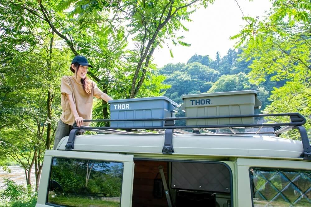 13_三沢真実さんがスズキ・エブリイのルーフ(天井)に登り、ルーフキャリアに手をかけている写真。THORのボックスが2つ並んで置かれており、おしゃれな雰囲気にまとまっている