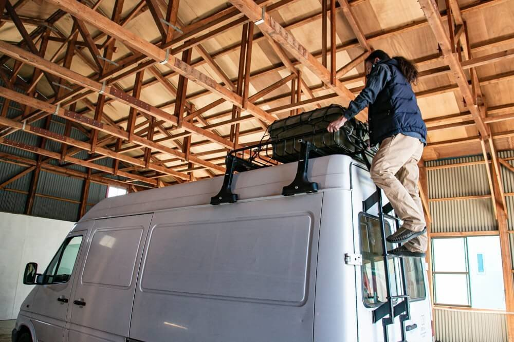 23_メルセデス・ベンツ「トランスポーターT1N」(ベントラ)のルーフ部分にクローズアップした写真。ルーフラダーに鈴木大地さんが登って「YAKIMA(ヤキマ)」のルーフラックにボックスを積載している