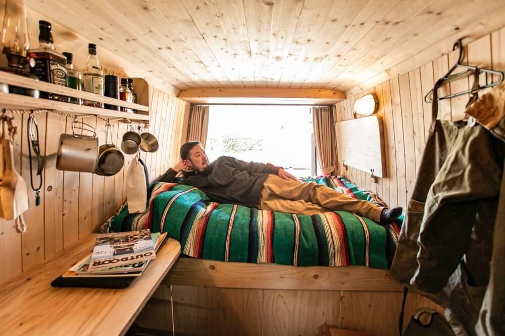 27_鈴木大地さんがカスタムしたメルセデス・ベンツ「トランスポーターT1N」(ベントラ)の車内。鈴木さんがベッドに寝転がっている