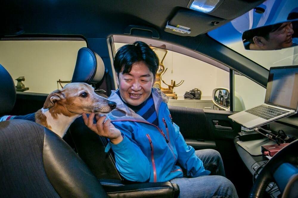 29_車中泊・キャンプの達人。小澤貴裕さんがカスタムしたHonda・フリードスパイクハイブリッドの運転席部分と愛犬の写真