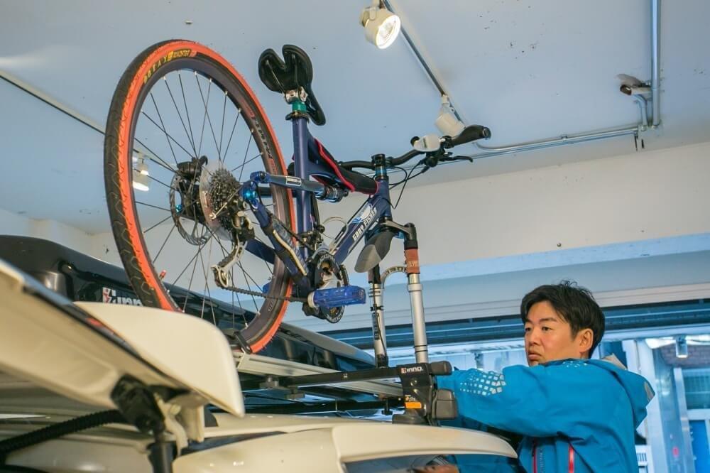 33_車中泊・キャンプの達人。小澤貴裕さんがカスタムしたHonda・フリードスパイクハイブリッドのルーフボックスの写真。マウンテンバイクの前輪を外してルーフボックスに固定している様子