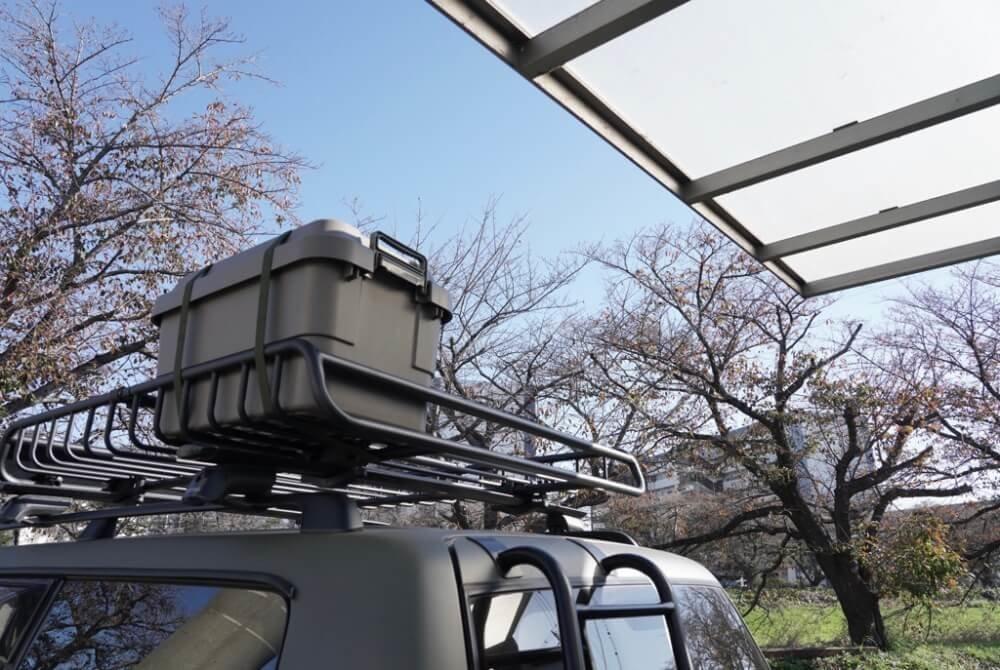 43_鈴木陽士さんがカスタムしたトヨタ・ランドクルーザーのルーフ部分写真。「YAKIMA(ヤキマ)」の「メガウォーリアー ルーフラック」にボックスを載せると高さが出ることを説明