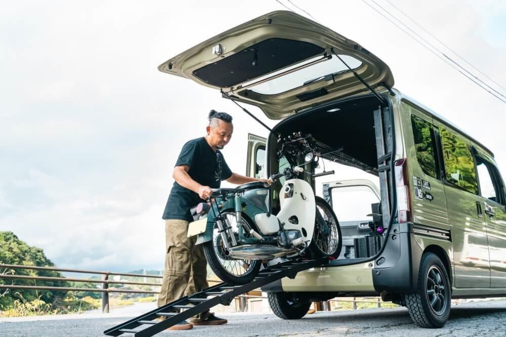 トランポ仕様にカスタムしたN-VANの助手席サイドに積まれたスーパーカブを車内から降ろすところ
