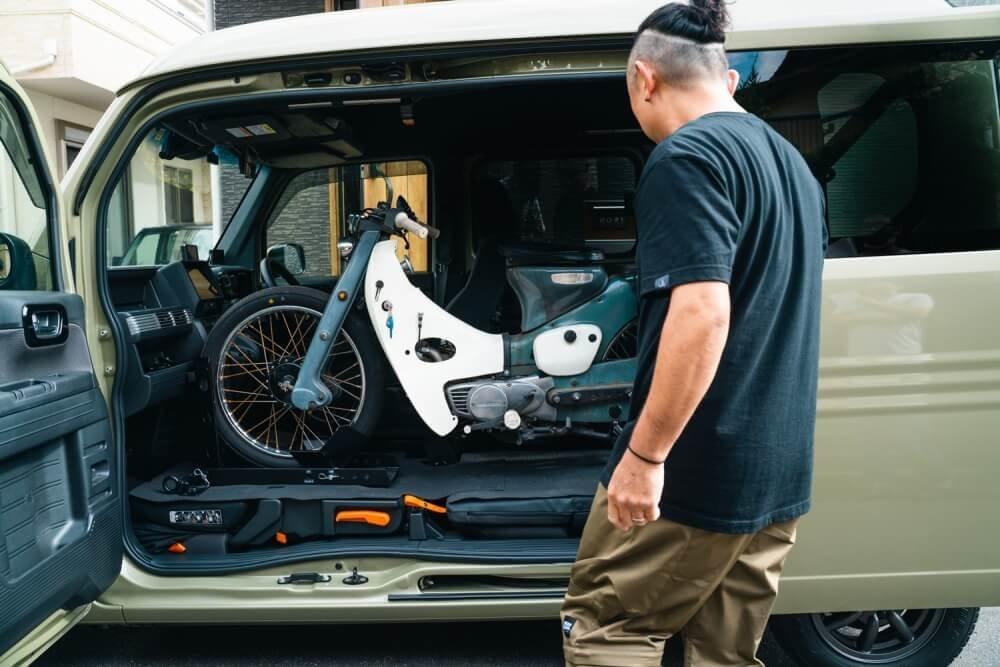 トランポ仕様にカスタムしたN-VANの車内に積み込まれたスーパーカブを見るオーナーの堀さん