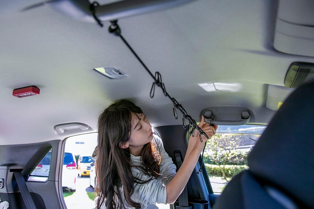 18_ホンダフィットのグラブレールにゴムロープを取り付けている森風美さん