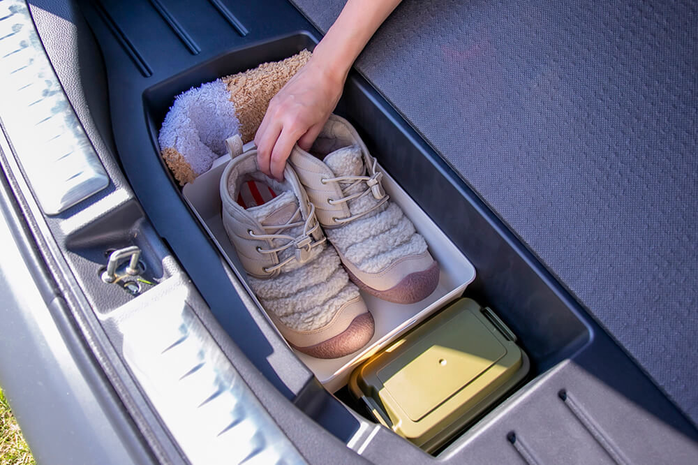 29_フィット クロスターの荷室の床下にある「カーゴフロアボックス」に靴を収納しているところ