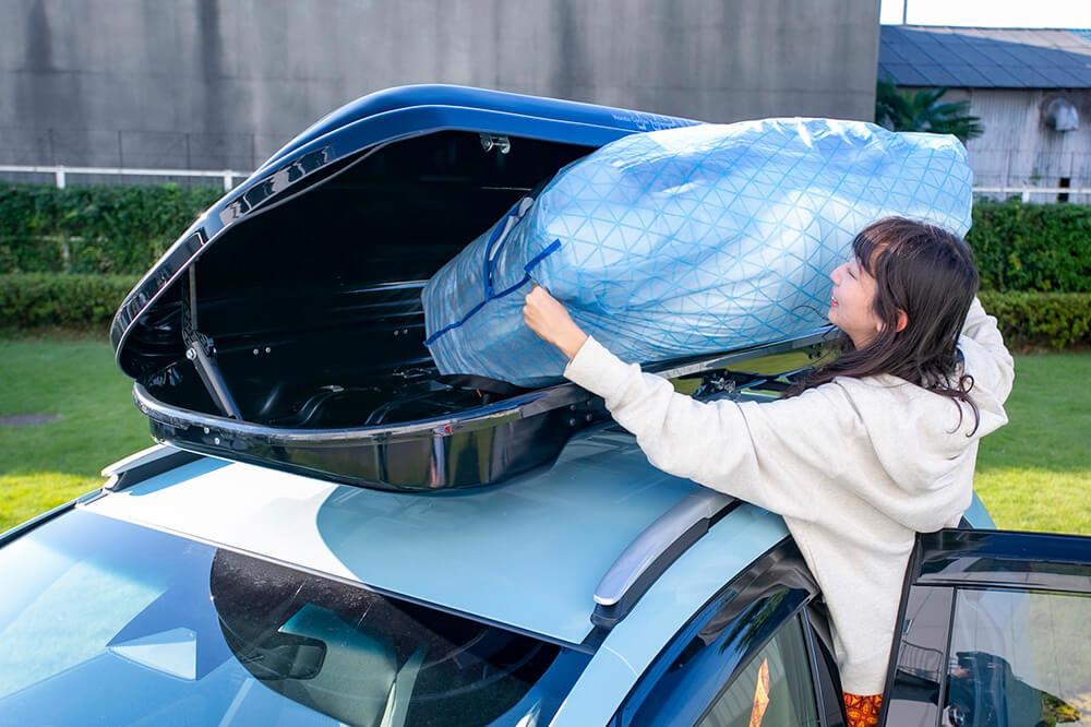 39_フィットクロスターのルーフボックスに布団を収納する森風美さん。布団はダイソーの布団ケースに入れて
